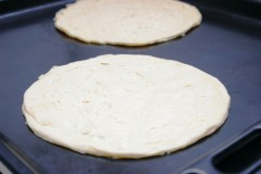 Roll out the dough into a flat pancake ready for cooking